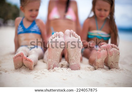 Closeup of the feet of mother and two daughters on the white sandy beach - stock photo