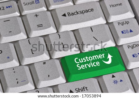 Closeup of the grey textured keys of a modern laptop computer keyboard.  One green colored key that is labeled Customer Service and includes an arrow. - stock photo