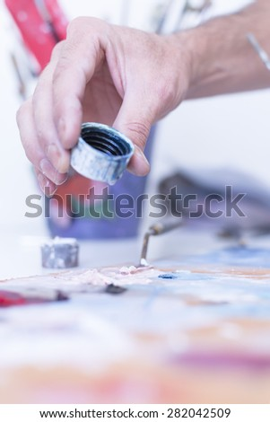 closeup of the hand of a male painter adding water to the paint over the palette - focus on the paint - stock photo