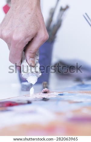 closeup of the hand of a painter adding paint to the palette at his painting studio - focus on paint - stock photo