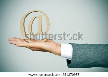 closeup of the hand of a young businessman showing an at sign - stock photo