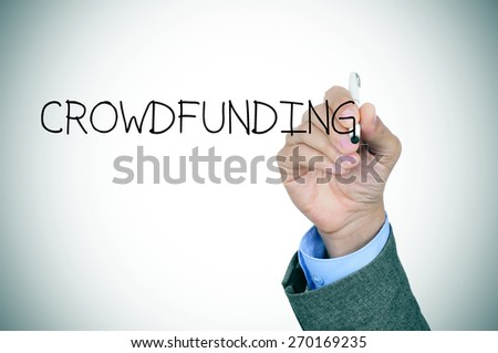 closeup of the hand of a young caucasian man in a grey suit writing the word crowdfunding in the foreground, slight vignette added - stock photo