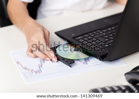 Closeup of the hand of a young woman inserting a cd in her laptop - stock photo