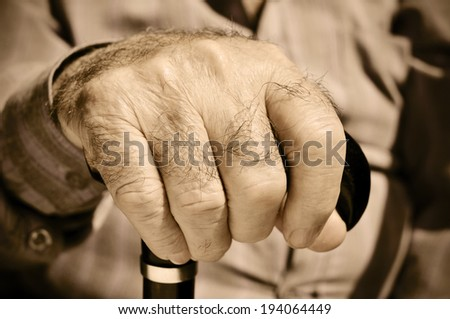 closeup of the hand of an old man with a walking stick - stock photo