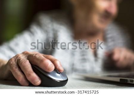 Closeup of the hand of an old woman holding a computer mouse. - stock photo