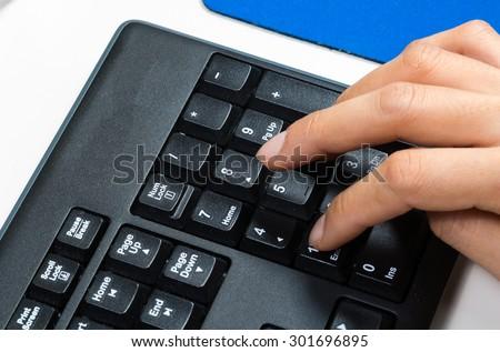 closeup of the hand  using the numeric keypad - stock photo