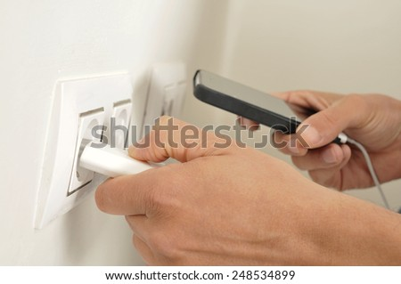 closeup of the hands of a man plugging in the plug of his smartphone in a socket - stock photo