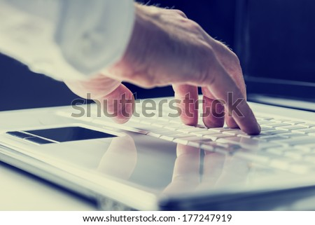 Closeup of the hands of a man typing on a laptop keyboard as he enters information or surfs the internet in an online communication and contact concept. With retro filter effect. - stock photo