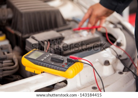 Closeup of the hands of a mechanic checking a car battery at an auto shop - stock photo
