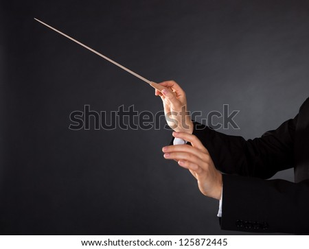 Closeup of the hands of a music conductor with a baton against a dark studio background with copyspace - stock photo