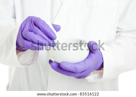 Closeup of the hands of a pharmacist or scientist, holding a mortar and pestle, and wearing rubber gloves. - stock photo