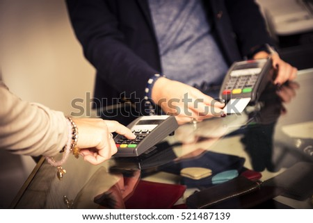 Closeup of the hands of a woman while is paying using a credit card in a shop