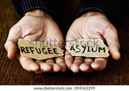 closeup of the hands of a young man with two pieces of paper with the words refugee and asylum written in each one, with a dramatic effect - stock photo