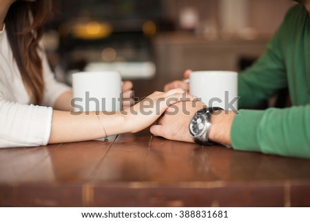 Closeup of the hands of a young woman holding the hands of her boyfriend while having coffee at a cafe - stock photo