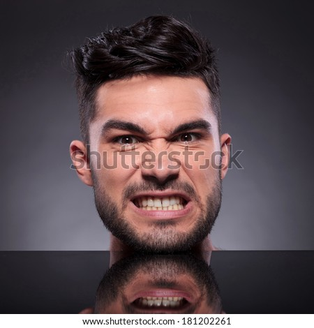 closeup of the head of a young man looking angry into the camera. on a black studio backgroud - stock photo