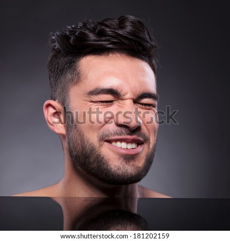 closeup of the head of a young man with a disgusted expression, with his eyes closed tightly. on a black studio backgroud - stock photo
