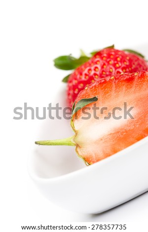 Closeup of the juicy flesh of a halved fresh ripe strawberry in a white ceramic bowl for use in cooking and baking as a healthy ingredient rich in vitamin C - stock photo