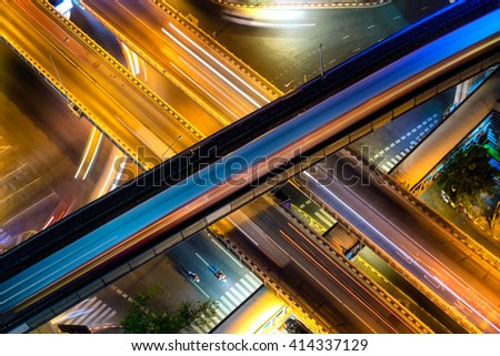 Closeup of the light trails on overpass in Bangkok, Thailand at night. X-Cross between highway and monorail  - stock photo
