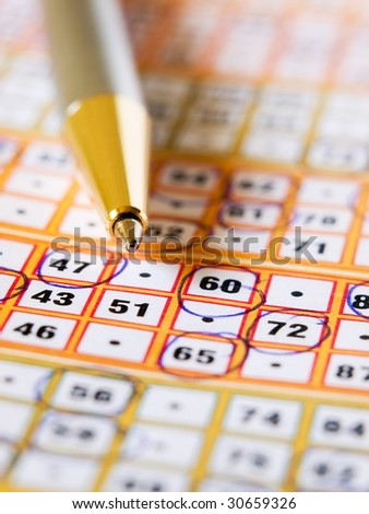 Closeup of the lottery ticket with a pencil on it. - stock photo
