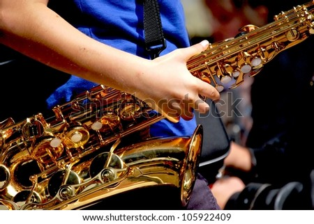 Closeup of the lower half of a tenor saxophone, holding with one hand by a teenager
