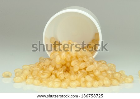 Closeup of the pot and group of soft gel capsules on white background - stock photo