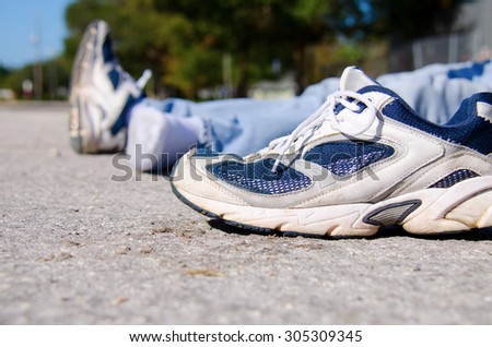 Closeup of the shoe from a pedestrian that is a victim of automobile hit and run on a roadside with the victim laying in the background. - stock photo