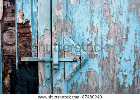 Closeup of the Side of a Blue Shed with Grey Weather-Worn Wood and Peeling Paint That Has Room for Text or Copy. - stock photo
