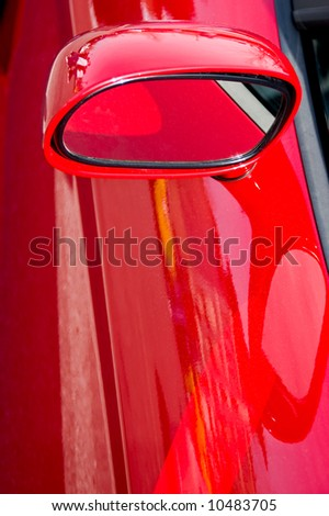 Closeup of the side view mirror on a red sports car - stock photo