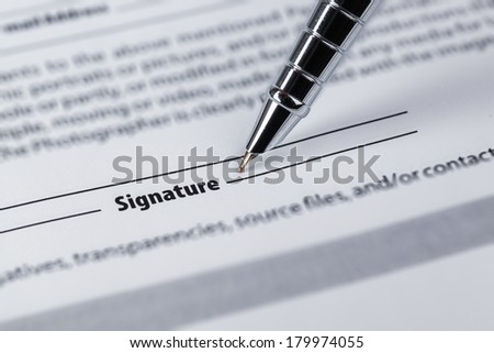 closeup of the signature and pen on a legal paper  - stock photo