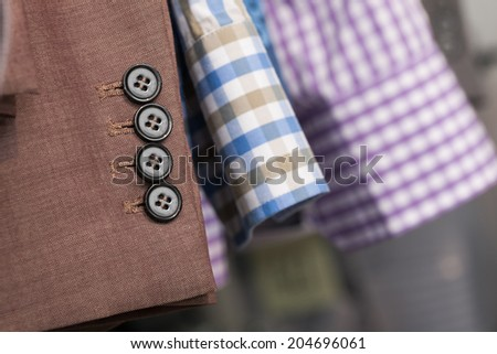 Closeup of the sleeves of a brown man coat and two blue and purple man shirts in a store or warehouse - stock photo