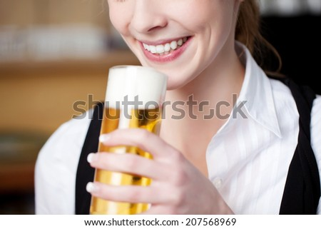Closeup of the smiling mouth of a woman with a frothy pint of beer in a glass in her hand - stock photo