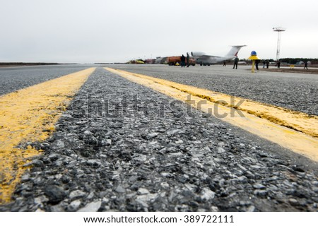 Closeup of the texture of the surface of the asphalt runway of a small airfield. Yellow markings. - stock photo