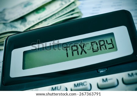 closeup of the the display of a calculator with the text tax day written in it and a pile of dollar banknotes in the background - stock photo