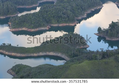Closeup of the water reflections in the water of the lakes at Guatape taken from Piedra el Penol with blue sky, near Medellin, Colombia. - stock photo
