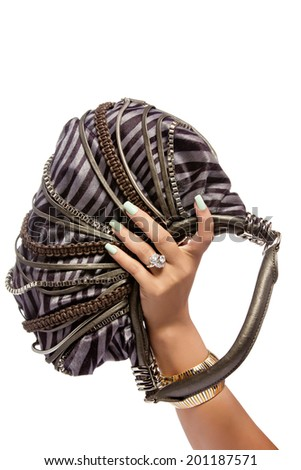closeup of the woman's hand wearing luxury ring, green nail art manicure with zebra stripes leather bag with silver chains, isolated on white studio background - stock photo