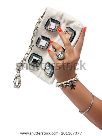 closeup of the womans hand wearing luxury ring, orange nail art manicure with white leather bag with silver chain bag, isolated on white studio background  - stock photo