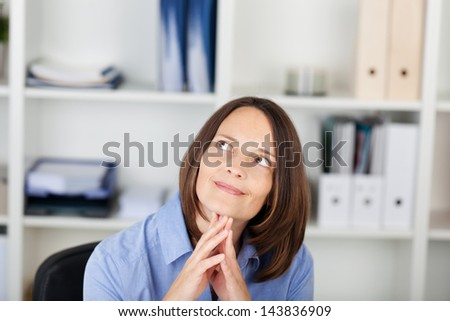Closeup of thoughtful businesswoman looking up in office - stock photo