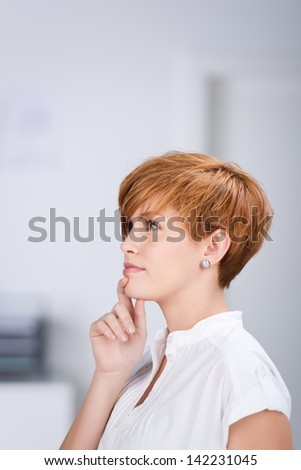 Closeup of thoughtful businesswoman with hand on chin looking away in office - stock photo