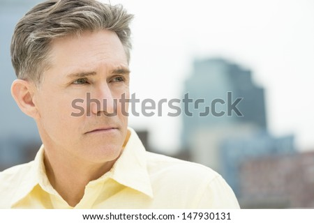 Closeup of thoughtful mature man looking away with buildings in background - stock photo