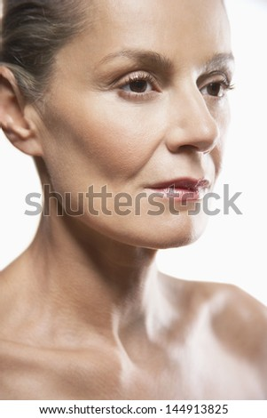 Closeup of thoughtful middle aged woman looking away on white background - stock photo
