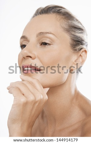 Closeup of thoughtful middle aged woman with hand on chin over white background - stock photo