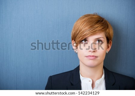closeup of thoughtful young businesswoman looking up isolated over blue background - stock photo