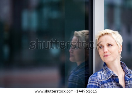 Closeup of thoughtful young woman looking away while leaning on glass - stock photo