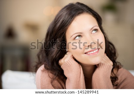 Closeup of thoughtful young woman looking up in house - stock photo