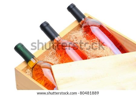 Closeup of three blush wine bottles on their side in a wooden crate. Crate lid is pulled partially back exposing the bottles and packing excelsior. Horizontal format isolated on white. - stock photo