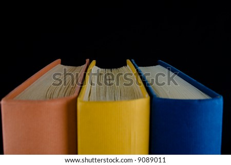 Closeup of three books,with orange, yellow and blue spines, lined up in a row. Isolated against black background. - stock photo