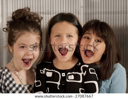Closeup of three cute young girls screaming - stock photo