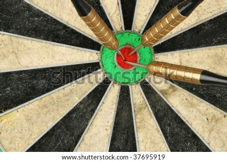 Closeup of three darts in center of a dartboard