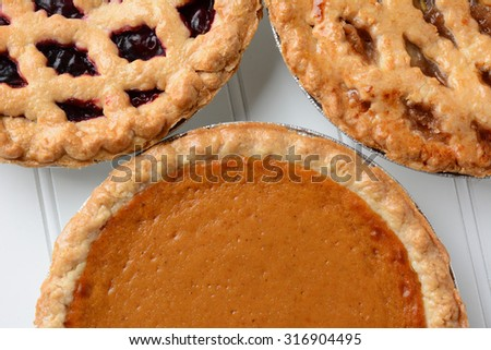 Closeup of three different fresh baked holiday pies.  Pumpkin, apple and a berry pie are shown. - stock photo