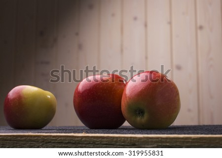Closeup of three fresh ripe delicious beautiful fruits with vitamins of red and yellow apple lying on wooden background, horizontal picture - stock photo